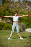 Dumbell exercise outdoors. Woman doing exercise with dumbell outdoors Stock Photo