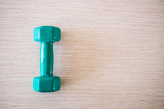 Dumbell. Green dumbell is on a table Stock Images