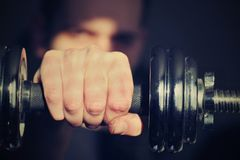 Dumbell with hand. Silver, hard dumbell in hand. Tool for fitness and exersice Royalty Free Stock Photo