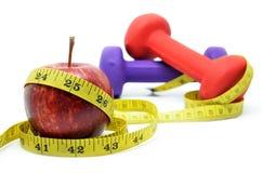 Dumbell met het meten van band en rode appel Stock Fotografie