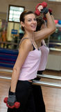 Dumbell Workout. A beautiful woman working out in a gym with red dumbells Stock Photos