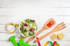 Dumbells、卷尺和健康食物 图库摄影