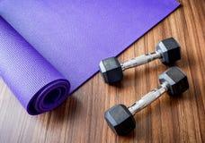 Dumbells和瑜伽席子在锻炼健身房 免版税库存图片