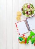 Dumbells, μέτρο ταινιών, υγιή τρόφιμα και σημειωματάριο για το διάστημα αντιγράφων Στοκ Φωτογραφία