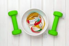 Dumbells и рулетка в шаре над деревянной предпосылкой Fitnes Стоковое Фото