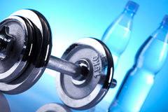 Dumbells. And bottles of water on the blue background Stock Image