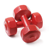 Dumbells. Small red plastic dumbells on white Stock Photos
