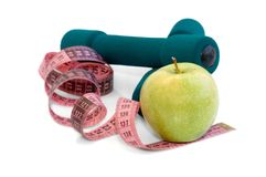 Dumbells, apple and measuring. Tape on a white background Royalty Free Stock Photos