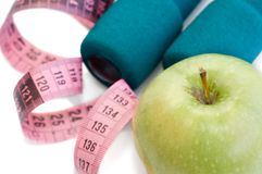 Dumbells, apple and measuring. Tape on a white background Stock Images