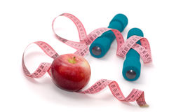 Dumbells, apple and measuring tape. On a white background Stock Photography