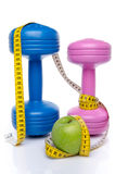 Dumbells and an apple with a tape measure Royalty Free Stock Photo
