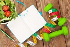 Dumbells, cinta métrica, comida sana y libreta para el espacio de la copia Fotografía de archivo libre de regalías