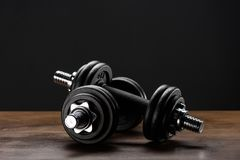 Dumbells. Closeup shot of two dumbells placed on dark wooden surface Royalty Free Stock Image