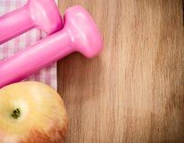 Dumbells e maçã cor-de-rosa na tabela de madeira Imagem de Stock