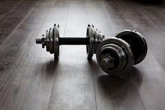Dumbells en piso de madera Fotografía de archivo