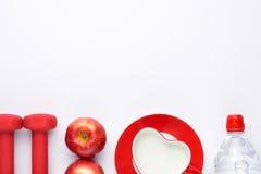 Dumbells, frutta fresca, bottiglia all'acqua di rose sopra fondo bianco Concetto di salute e di forma fisica Vista da sopra Vista Immagini Stock