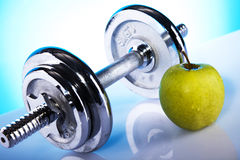 Dumbells and green apple. Dumbells andgreen apple on the blue background Royalty Free Stock Image
