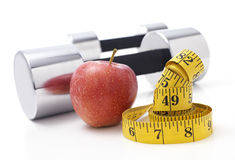 Dumbells. Gym Dumbells with an Apple and tape measure Royalty Free Stock Photos