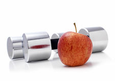 Dumbells. Gym Dumbells with an Apple on a white background Royalty Free Stock Images