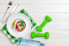 Dumbells and healthy food over wooden background Stock Photos