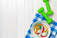 Dumbells and healthy food over wooden background Stock Photography