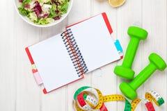 Dumbells, Maßband, gesundes Lebensmittel und Notizblock für Kopienraum Lizenzfreies Stockfoto