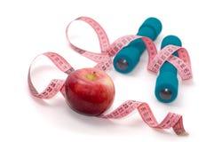 Dumbells, manzana y cinta de medición Fotografía de archivo