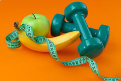 Dumbells met het meten van band en vruchten stock afbeeldingen