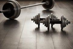 Dumbells per forma fisica sul pavimento di legno Fotografie Stock