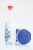 Dumbells revestidos e garrafa de água do plástico azul Fotos de Stock Royalty Free