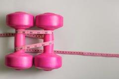 Dumbells roses de dames avec la bande de mesure Images libres de droits
