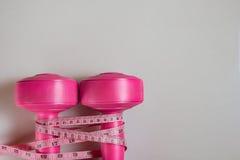 Dumbells roses de dames avec la bande de mesure Photo libre de droits