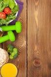 Dumbells, ruban métrique et nourriture saine au-dessus de fond en bois Photographie stock libre de droits