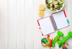 Dumbells, ruban métrique, nourriture saine et bloc-notes pour l'espace de copie Images stock
