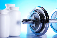 Dumbells and supplements of diet. On the blue background Stock Photos