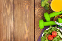 Dumbells, tape measure and healthy food. Fitness and health. Dumbells, tape measure and healthy food over wooden background. Fitness and health. View from above Royalty Free Stock Photography