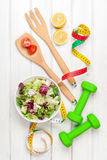 Dumbells, tape measure and healthy food. Fitness and health. View from above over wooden table Stock Photography