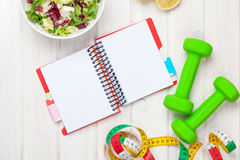 Dumbells, tape measure, healthy food and notepad for copy space Royalty Free Stock Photo