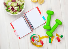 Dumbells, tape measure, healthy food and notepad for copy space Stock Photography