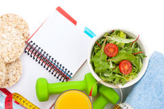 Dumbells, tape measure, healthy food and notepad for copy space. Stock Photography