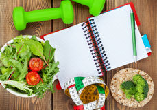 Dumbells, tape measure, healthy food and notepad for copy space. Stock Image