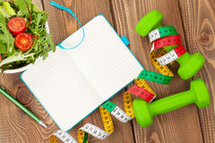Dumbells, tape measure, healthy food and notepad for copy space. Royalty Free Stock Photography