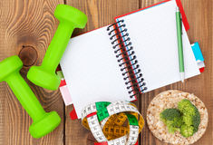 Dumbells, tape measure, healthy food and notepad for copy space. Royalty Free Stock Image