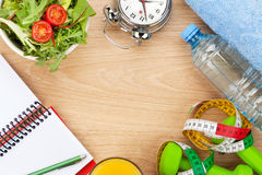 Dumbells, tape measure and healthy food over wooden background Stock Images