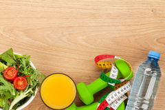 Dumbells, tape measure and healthy food over wooden background Royalty Free Stock Photo