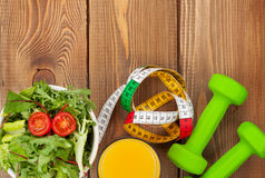 Dumbells, tape measure and healthy food over wooden table Stock Images