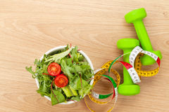 Dumbells, tape measure and healthy food over wooden table Stock Photos