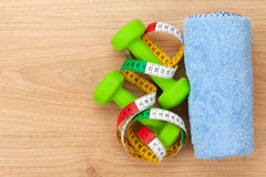 Dumbells and tape measure over wooden table with copy space Royalty Free Stock Images