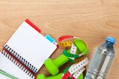 Dumbells, tape measure, water bottle and notepad for copy space Royalty Free Stock Images