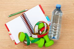 Dumbells, tape measure, water bottle and notepad for copy space Royalty Free Stock Photos